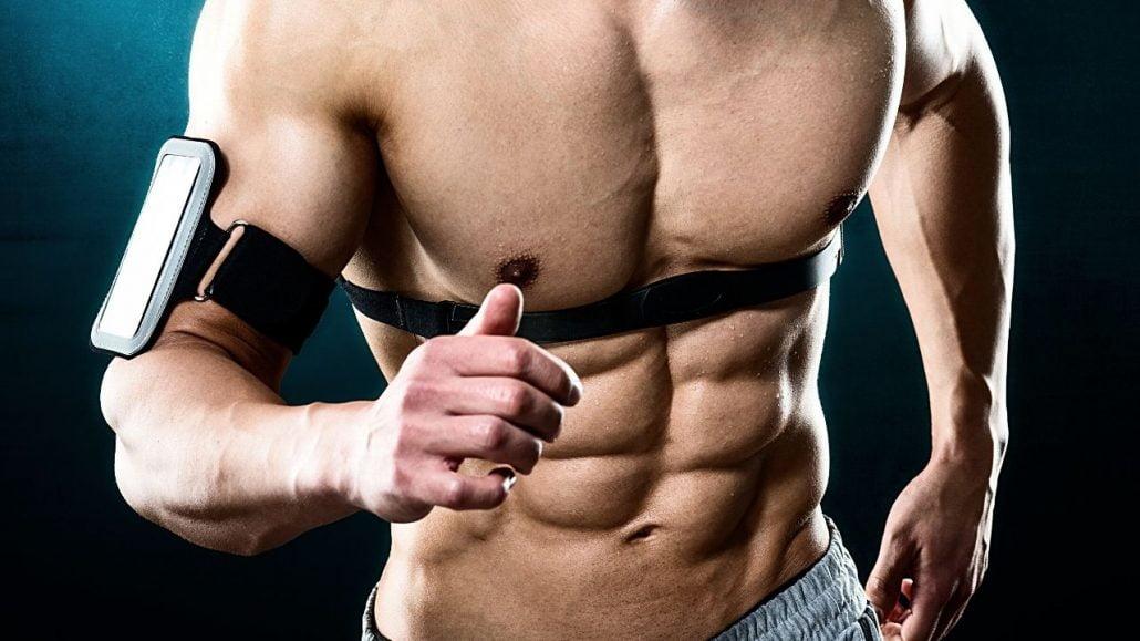 Seorang pria memasang belt di area dada dan bicep untuk mengukur detak jantung saat melakukan aktivitas olahraga