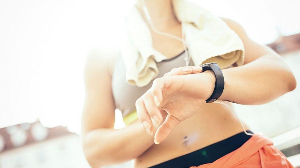 Seorang wanita sedang mengecek detak jantung saat olahraga melalui smartwatch